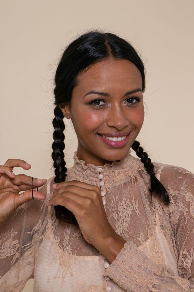modelo morena de cabelo preto longo e levemente ondulado com duas tranças baixas