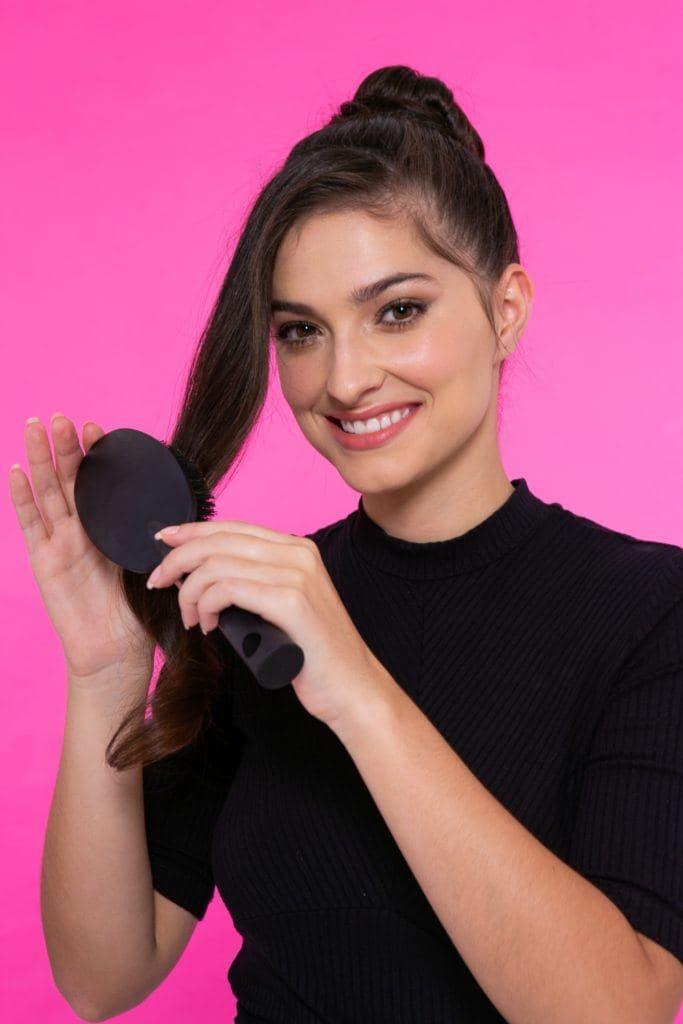 modelo de cabelo preto, liso e longo em fundo rosa com um coque penteando a mecha frontal