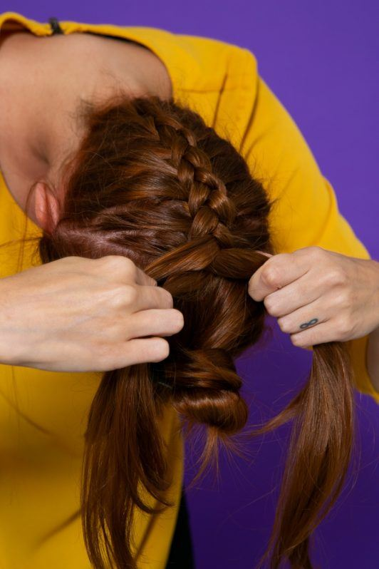 modelo de cabelo ruivo e liso fazendo uma trança invertida