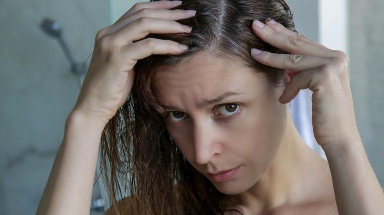 Mulher olha para a raiz do cabelo onde aparecem fios brancos, provavelmente causados pela falta de melanina no cabelo