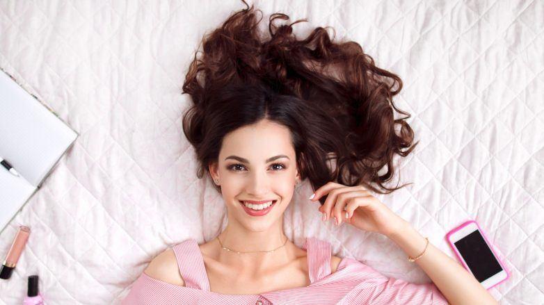 mulher deitada na cama com cabelo brilhante