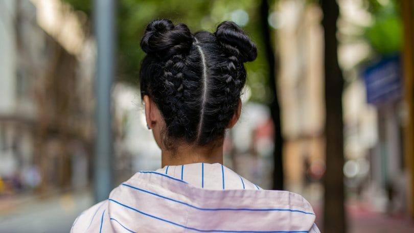 modelo com tranças de cabelo invertidas com coque duplo