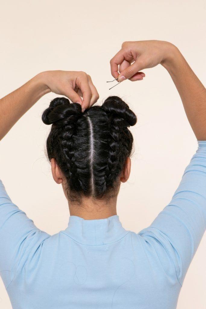 modelo com tranças no cabelo invertidas com coque duplo