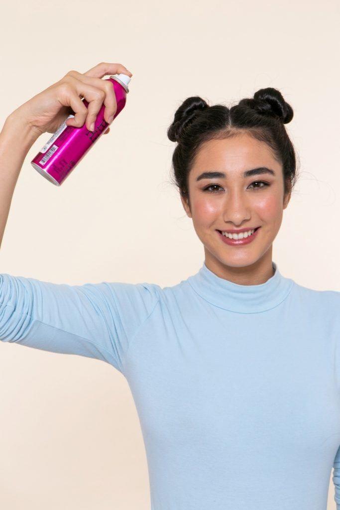 modelo com tranças no cabelo invertidas com coque duplo aplicando shampoo a seco