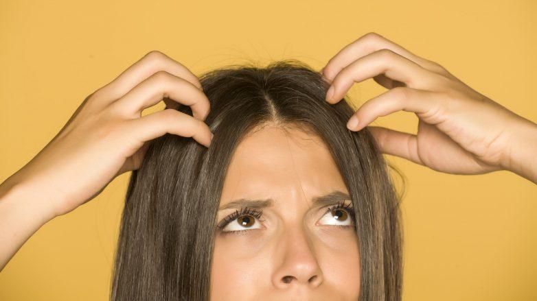 Mulher com a mão no couro cabeludo