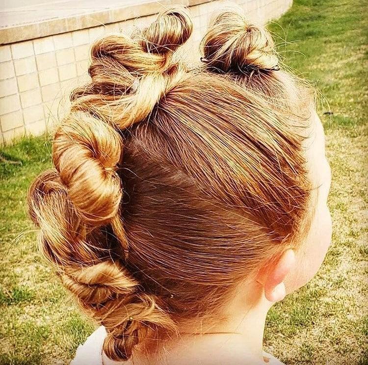 Menina com penteado de moicano com coques