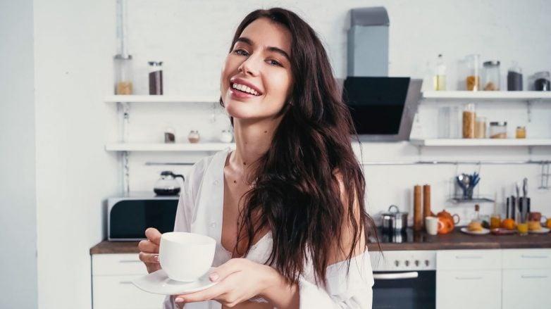 mulher com cabelo longo na cozinha tomando café e sorrindo