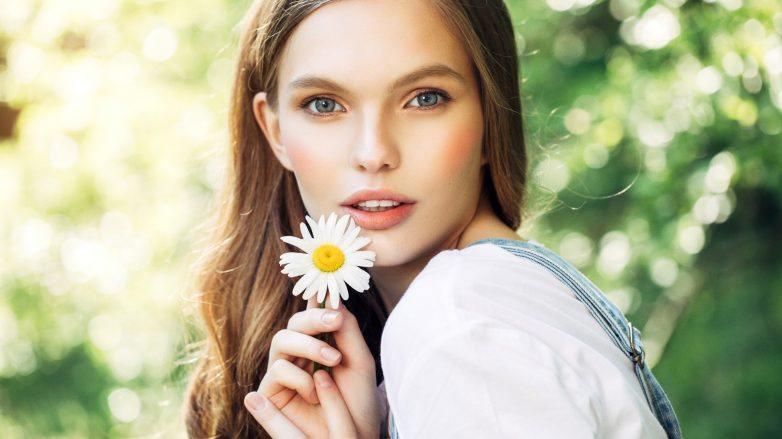 Mulher com cabelos loiros escuros segura flor em suas mãos