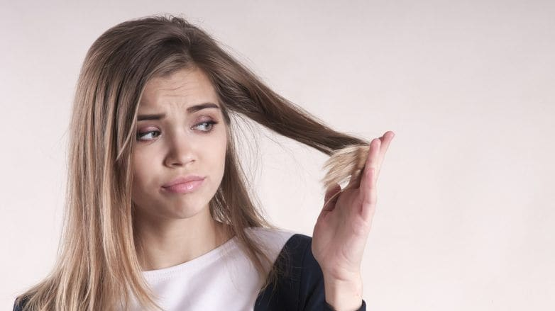 mulher olhando preocupada para os cabelos secos