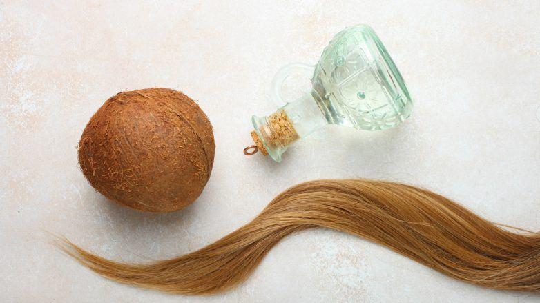 Foto com mecha de cabelo loira, óleo de coco em um frasco e o coco inteiro