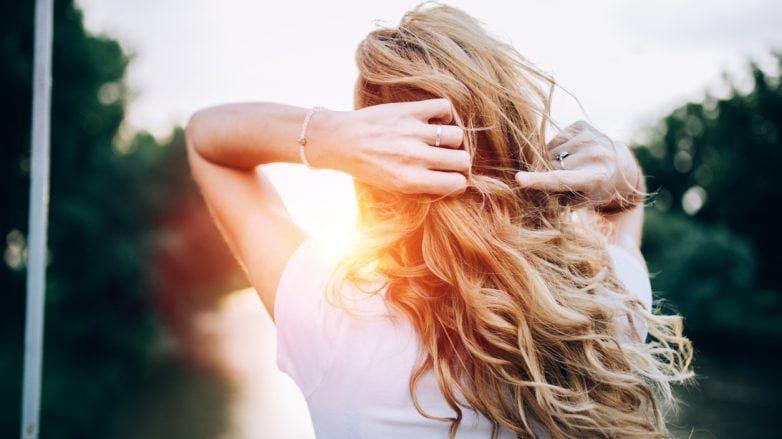 mulher de costas com cabelo longo ondulado loiro