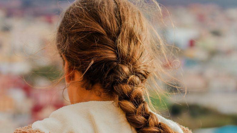 Mulher com trança e frizz no cabelo vista de costas