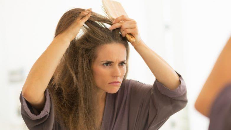 Mulher olha para o cabelo quebrado na frente no espelho