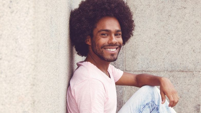 homem com cabelo crespo sentado sorrindo