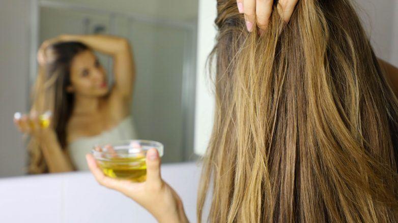 mulher passando azeite no cabelo