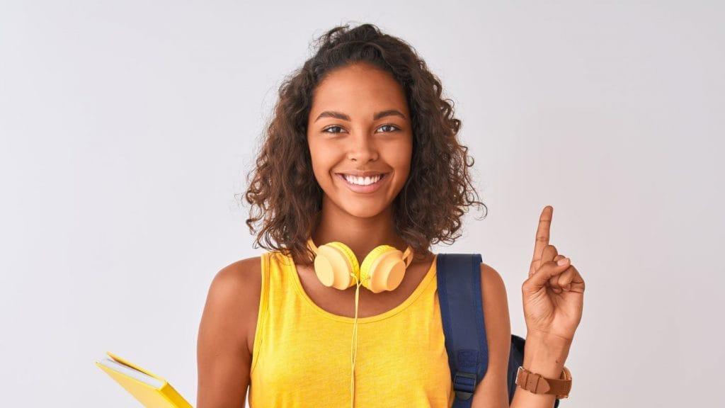 Garota com cabelos cacheados na altura dos ombros aponta o dedo para o alto