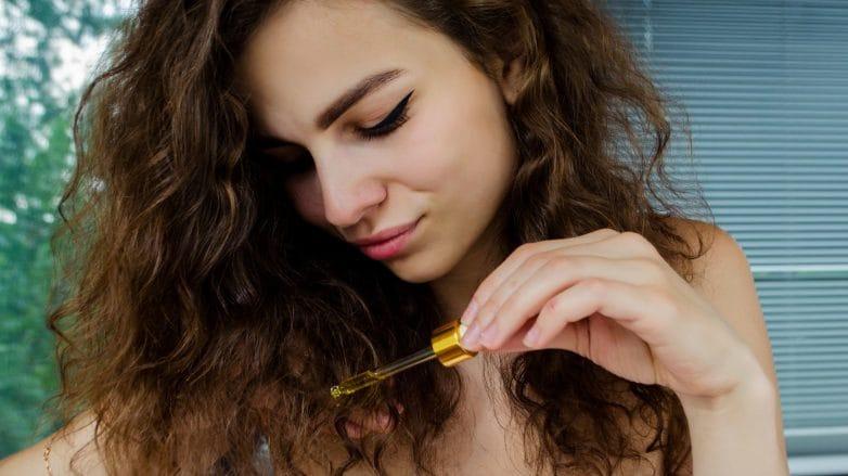 Mulher aplicando óleo nas pontas de seu cabelo