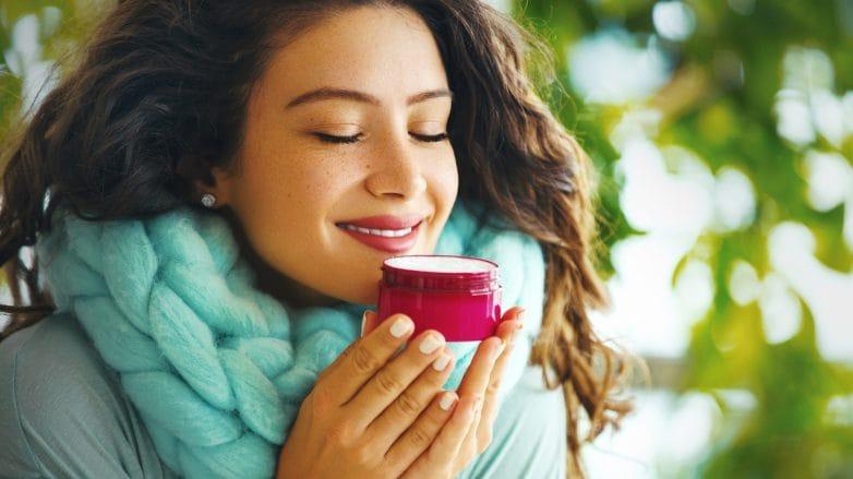 Mulher apreciando o cheiro de um creme hidratante