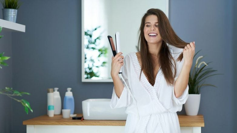 mulher arrumando o cabelo no banheiro