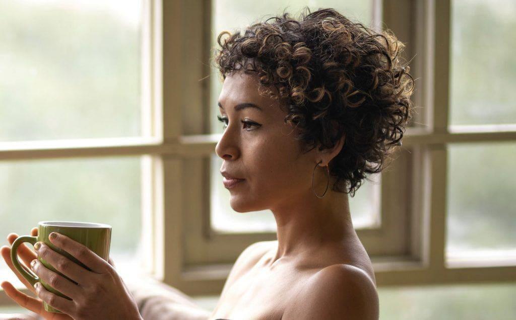 Mulher dentro da banheira, olhando pela janela e segurando xícara