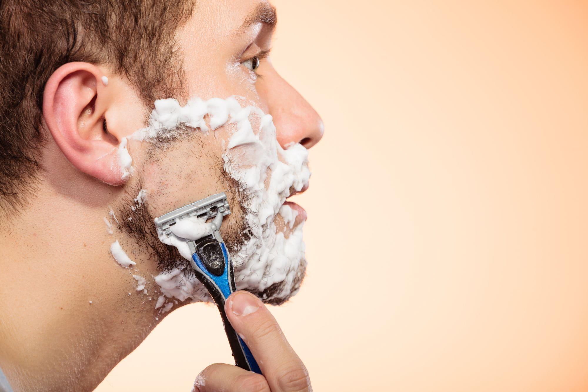 Homem fazendo a barba com lâmina de barbear