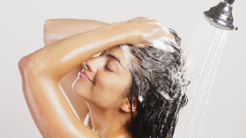 Mulher passa shampoo nos cabelos e faz espuma durante o banho