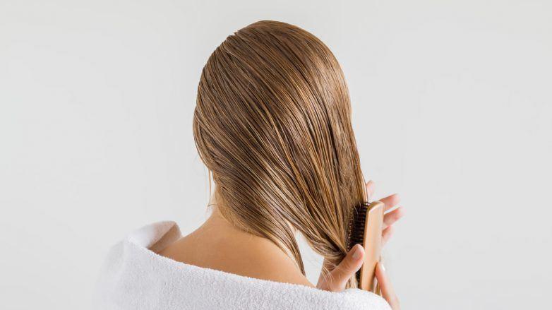 Mulher vista de costas penteia os cabelos loiros molhados