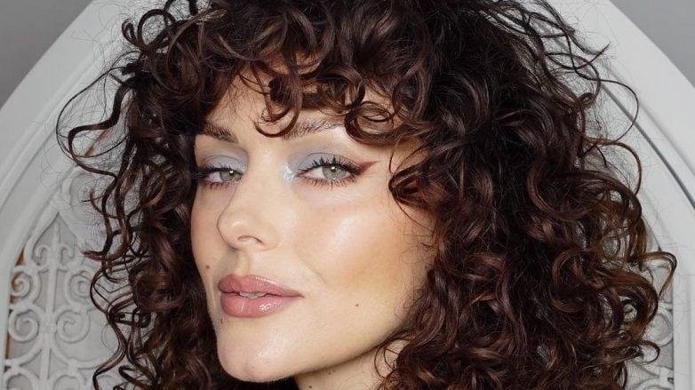 mulher com cabelo encaracolado com franja castanho