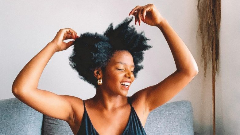 influenciadora toca os cabelos crespos curtos