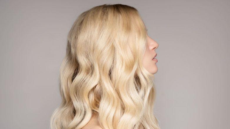mulher com cabelo loiro ondulado longo
