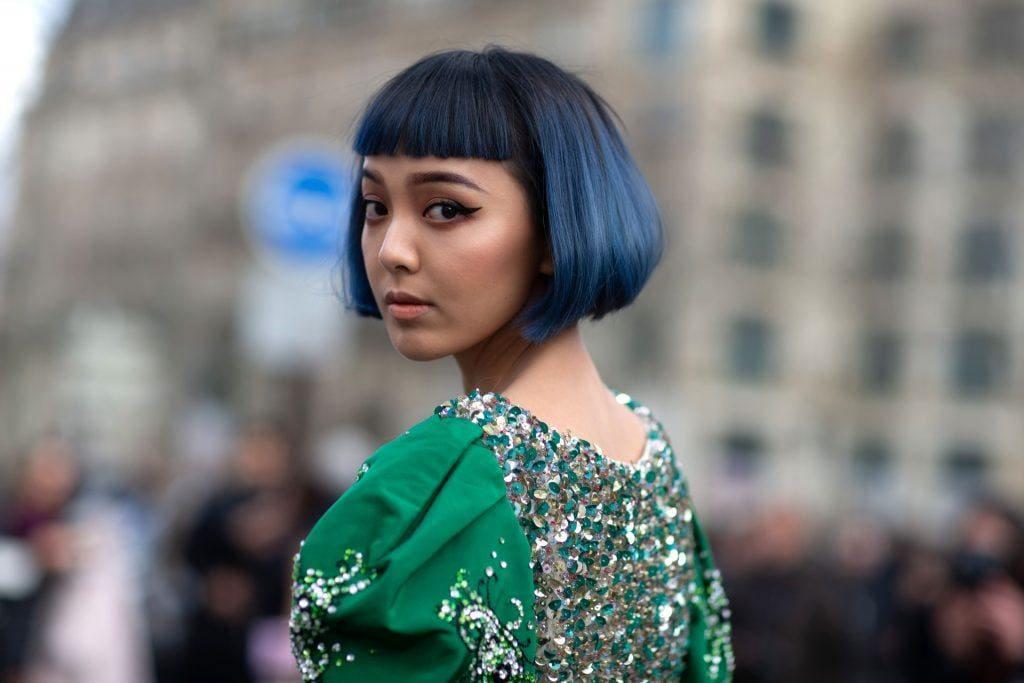 Mulher com traços orientais de cabelo curto, franja e cor azul olha para trás em direção à câmera
