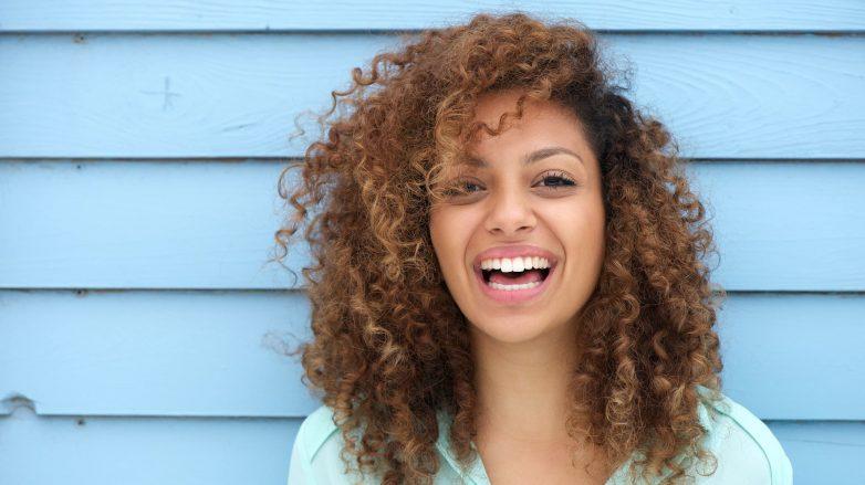 Mulher de cabelo cacheado com franja longa sorri. Ela usa camisa azul e está em frente a parede de madeira também azul