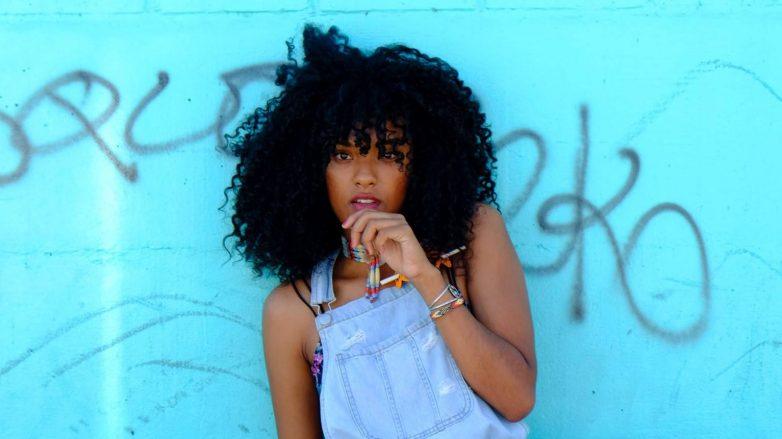 Mulher com cabelos cacheados com texturização veste macacão jeans. Ela faz pose com a mão perto do rosto. em frente a um muro azul pichado