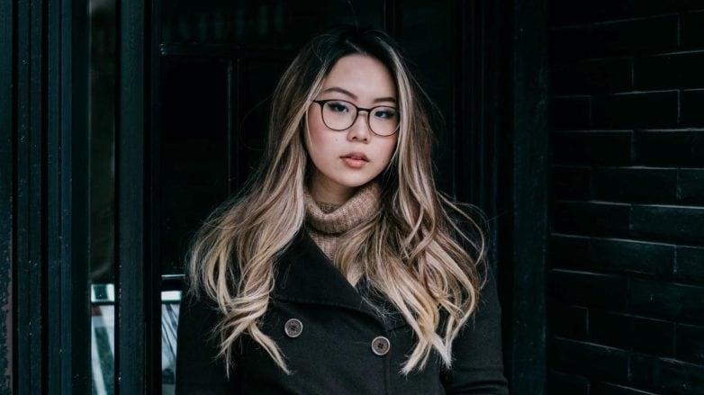 Mulher de cabelos longos e óculos usa roupa de frio. Ela está em pé, na entrada de um prédio