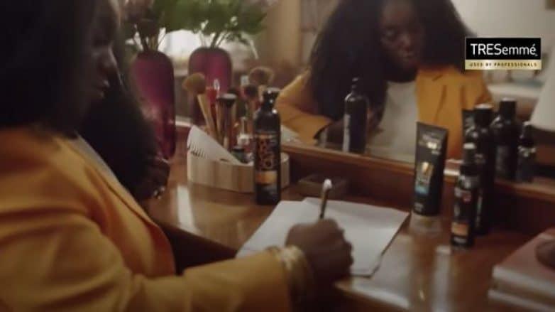 mulher escrevendo em papel com produtos tresemmé na mesa