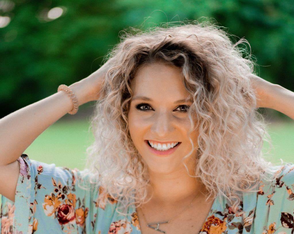Mulher loira de cabelos cacheados sorri, com as duas mãos no cabelo. Atrás dela há um gramado e árvores