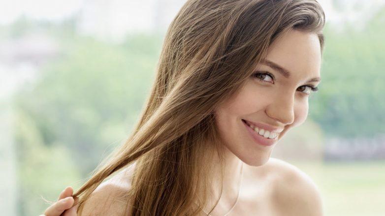 Mulher sorri, segurando mecha de cabelo