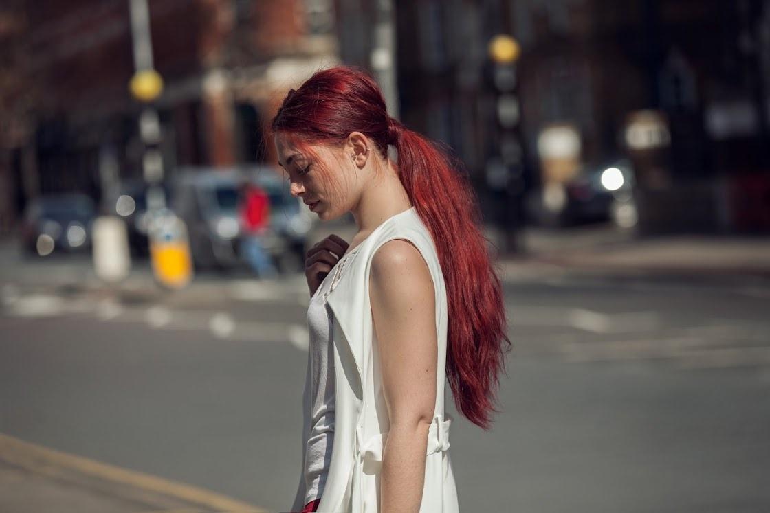 a long red ponytail girl walking on the street wearing white dress