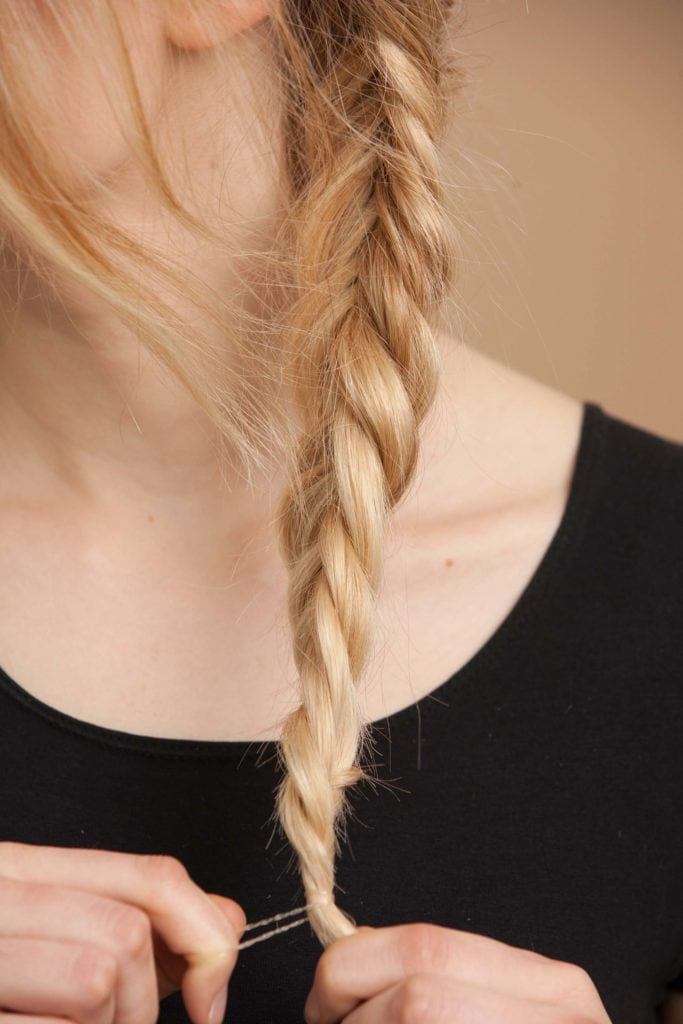 blonde woman creates fishtail braid and secures the braid