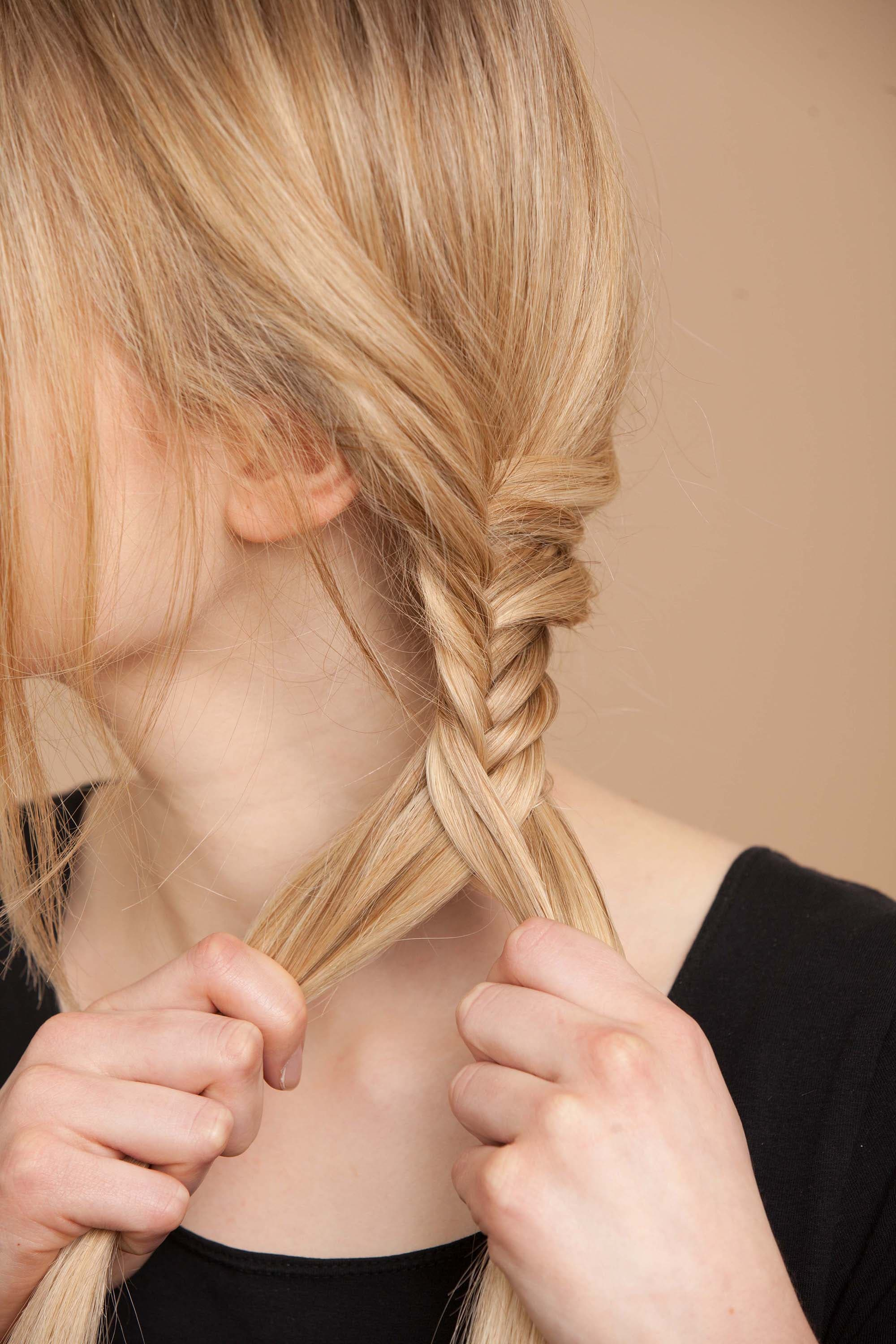 blonde woman creates fishtail braid and continues plait