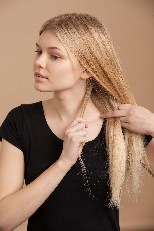 blonde woman creates fishtail braid and begins fishtail