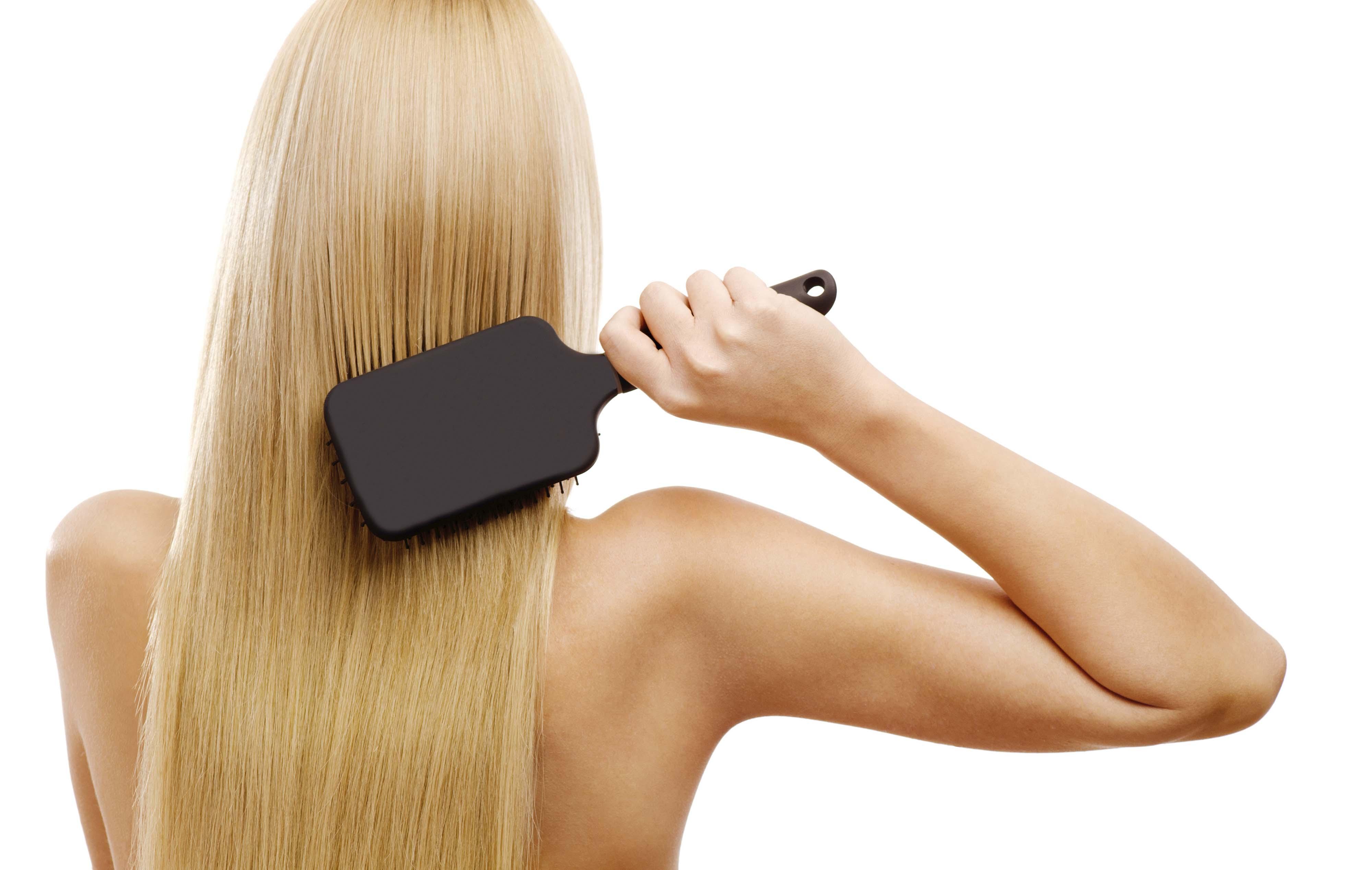 blonde woman using paddle brush to brush hair