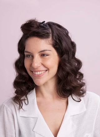 brunette woman wears 1950s hairstyles and curls top hair