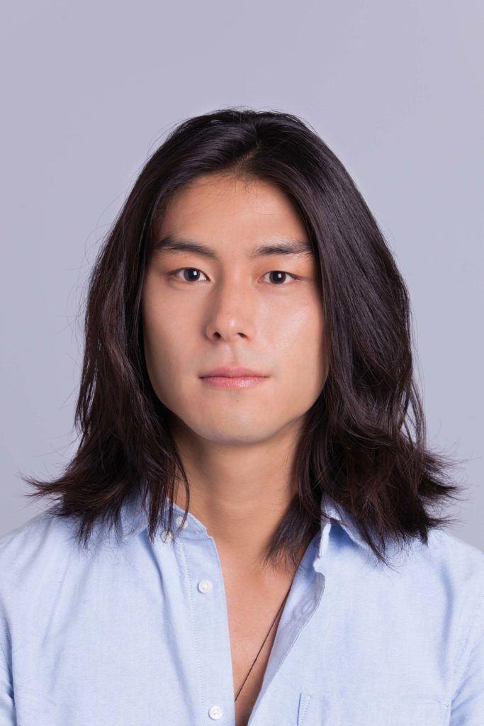 man creates asian man bun on clean hair