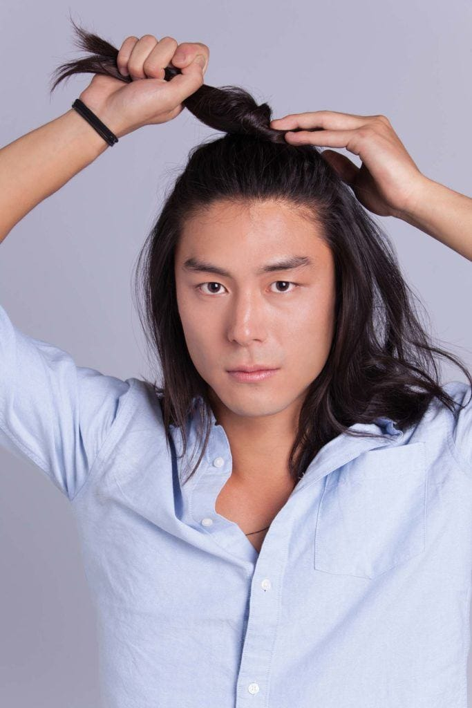 man creates asian man bun and twists hair