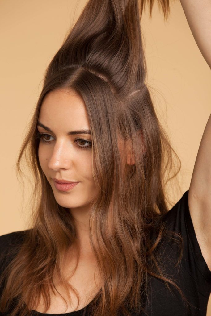 woman with light brown hair creates beehive hair and works in sections