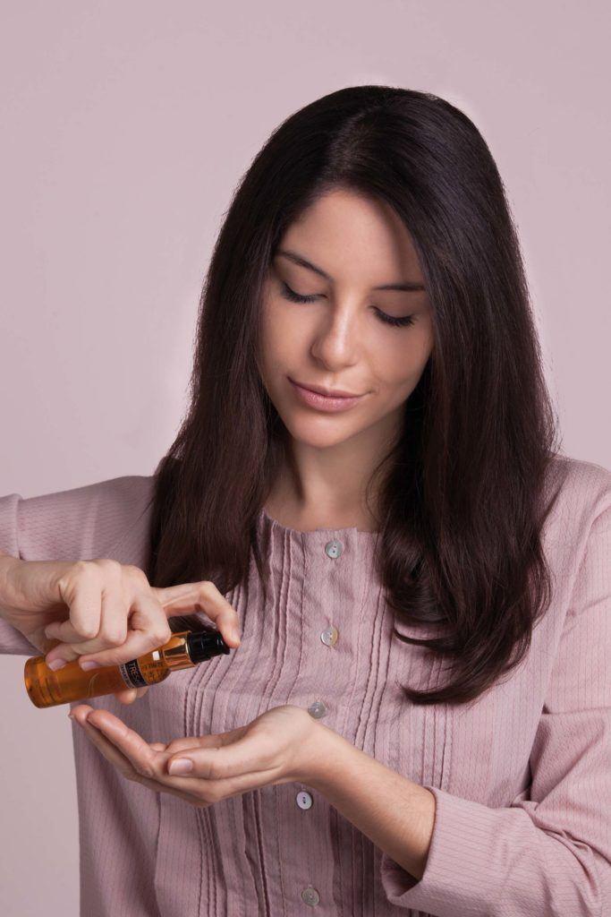 a beautiful bride applying hair serum