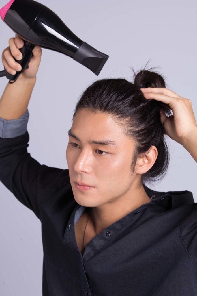 asian man creates cool hairstyles for men and blow dries