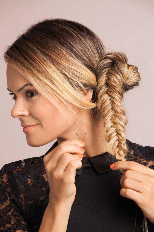 blonde woman creates side fishtail bun hairstyles and makes a bun