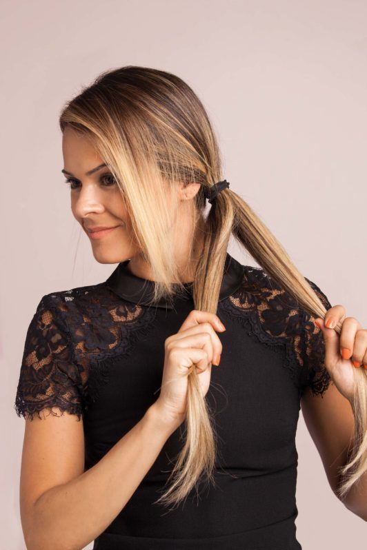 blonde woman creating side fishtail braid